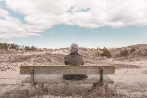 Older person sitting on bench near sand dunes